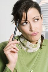 Frau jung mit Stift an Kopf, Wegschauen, close-up