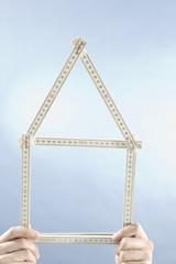 Hände halten einen Zollstock, Form eines Hauses