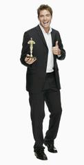 Junger Mann mit Filmpreis, Oscar, Daumen hoch