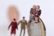 Figuren, älteres Paar, Senioren, Senioren sitzen auf Münze, junges Paar im Hintergrund