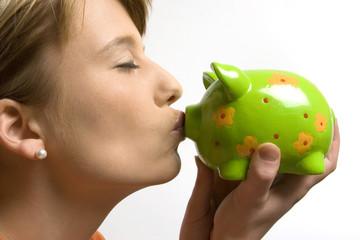 Junge Frau küsst Sparschwein