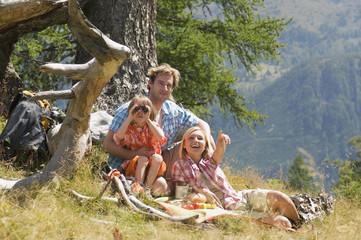 Österreich, Salzburger Land, Eltern und Sohn beim Picknick