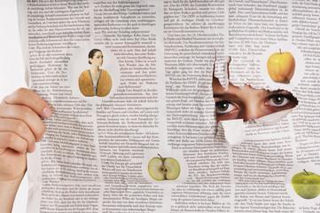 Frau schaut durch zerrissene Zeitung