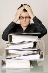 Erwachsene Frau mittleren Alters mit Dokumenten auf dem Schreibtisch