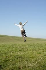 Frau springt auf der Wiese, Rückansicht