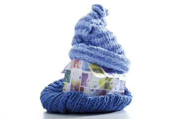 Haus aus Euro-Scheinen in Schal und Mütze eingewickelt