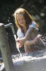 Mädchen spielt mit Wasser eines Brunnens
