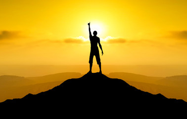 Champion on mountain peak during sunrise