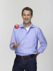 Junger Mann spielen mit dem Apfel, Portrait