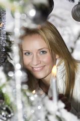 Österreich, Salzburger Land, Junge Frau am Weihnachtsbaum