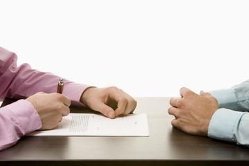 Geschäftsleute sitzen am Konferenztisch, einander gegenüber