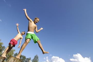 Österreich, Jungs springen von Baumstämmen ins Wasser