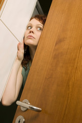Junge Frau späht durch Tür