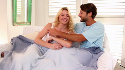 Affectionate couple sitting on sofa under blanket