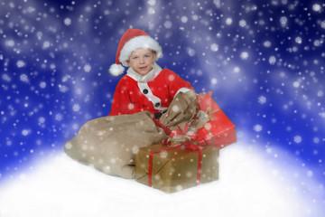 Junge im Weihnachtsoutfit vor Geschenken
