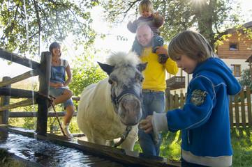 Familie mit Pony, am Brunnen