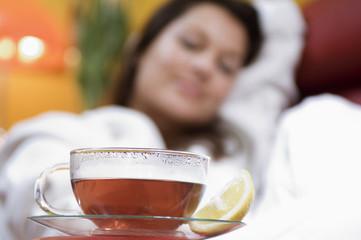 Frau sitzt im Stuhl mit einer Tasse Tee