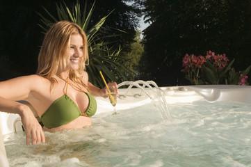Frau in der Badewanne mit Getränken, lächelnd