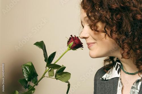 Frau riecht an Rose, Seitenansicht