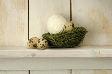 Ostereier liegen auf Nest im Regal