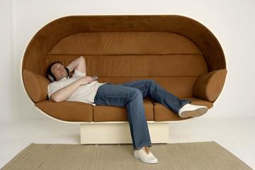 Mann entspannen auf dem Sofa mit Kopfhörern und Fernbedienung