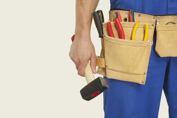 Mann tragen Werkzeuggürtel und mit Hammer, close-up
