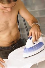 Mann bügelt Hemd