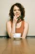 Junge Frau sitzt am Tisch mit Kaffeetasse