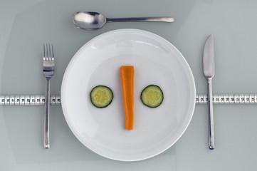 Teller mit Karotten und Gurken mit Maßband