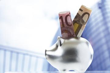 Geldschein ragt aus Sparschwein