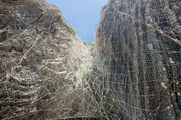Metallic grid on rocks to prevent collapse in Cinque terre
