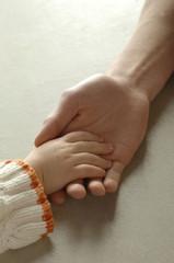 Vater hält die Hand des Kindes