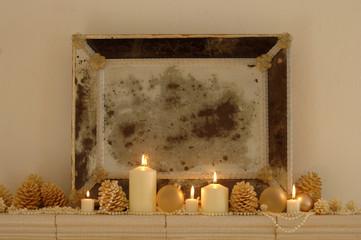 Brennende Kerzen mit Tannenzapfen und Bilderrahmen auf dem Regal, close-up
