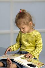 Kleines blondes Mädchen liest in einem Buch für Kinder
