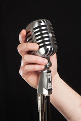 hand holding a retro microphone over black background