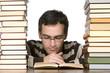 Junger Mann liest unter einem Stapel Bücher