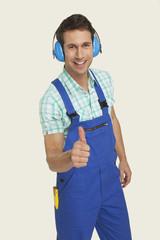 Mann tragen Ohrenschutz zeigen Daumen hoch Lächeln, Portrait