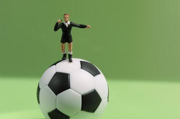 Schiedsrichterfigur, stehend auf Fußball