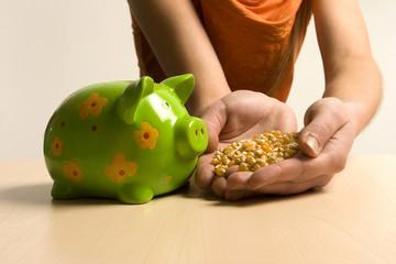 Junge Frau füttert ihr Sparschwein mit Mais
