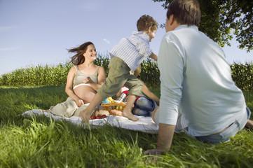 Eltern mit zwei Kindern beim Picknick