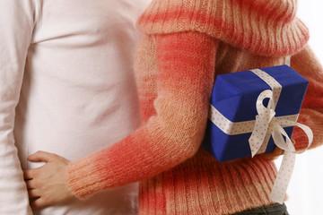 Frau versteckt ein Geschenk für IHN hinter dem Rücken