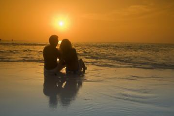 Paar sitzt am Strand, Silhouette bei Sonnenuntergang, Malediven