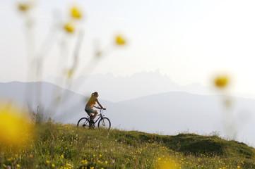 Österreich, Frau fährt Fahrrad über eine Wiese