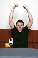 Junger Mann vor dem Fernseher, schaut Fußballspiel mit Chips