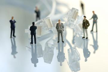 Business-Männer-Figuren stehen neben Kabeln
