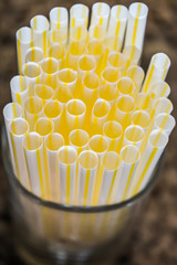 Group of plastic drinking straws in a glass