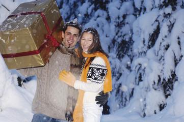 Mann zieht Frau mit Geschenk auf Schlitten, Seitenansicht