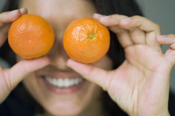 Frau jung mit Mandarinen auf Augen