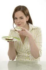 Junge Frau isst ein Brot mit Frischkäse und Schnittlauch