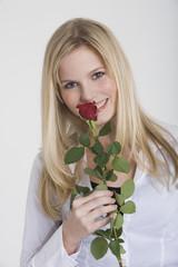 Frau jung halten eine Rose, lächeln, Porträt
